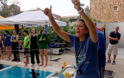 Coach Beck cheers on the swim team