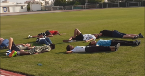 A group of Gen Z students lie down to de-stress on the grass after a long day at school.