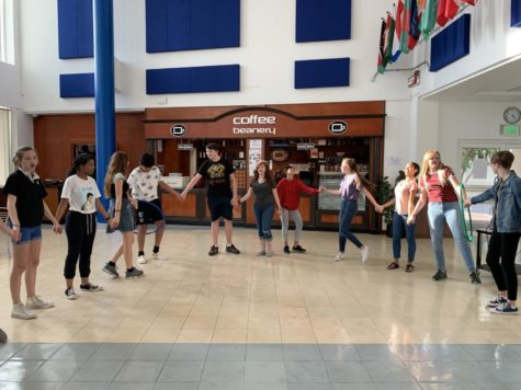 The 9th graders passing around a hula-hoop.