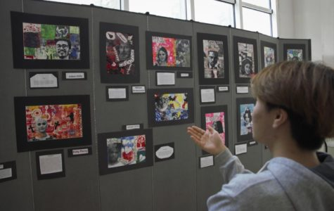 High school junior C. Kim admires the work MS art students put into designing work about role models (OR CELEBRITIES?? HEROES?). Students tried to capture the essence of human icons with their artistic gel paints.