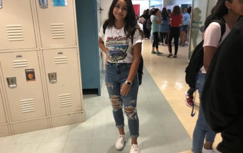 F. Manieri ('22) is shown wearing a white graphic tee tucked into blue ripped jeans. The rolls in her jeans and shirt add a cute and cleaned-up effect to the outfit.