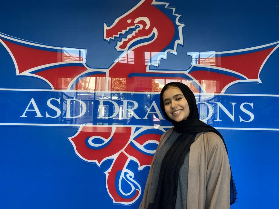 J.+Ahmed+stands+in+front+of+ASD+Dragons+logo%2C+showing+her+ASD+pride.+